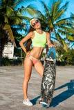 Πλήρες μήκος της νέας μοντέρνης γυναίκας στα γυαλιά που στέκονται με skateboard και που κοιτάζουν στη κάμερα Στοκ εικόνες με δικαίωμα ελεύθερης χρήσης