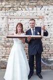 Πλήρες μήκος της νύφης και του νεόνυμφου που κοιτάζουν μέσω του πλαισίου πορτρέτου Στοκ Εικόνες