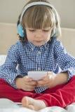 Πλήρες μήκος της χαριτωμένης μουσικής ακούσματος αγοριών στα ακουστικά στην κρεβατοκάμαρα Στοκ εικόνες με δικαίωμα ελεύθερης χρήσης