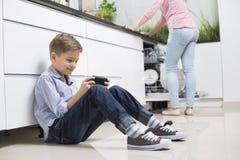 Πλήρες μήκος του αγοριού που χρησιμοποιεί το φορητό τηλεοπτικό παιχνίδι με τη μητέρα στο υπόβαθρο στην κουζίνα στοκ φωτογραφία