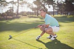 Πλήρες μήκος του ατόμου παικτών γκολφ που τοποθετεί τη σφαίρα γκολφ στο γράμμα Τ Στοκ φωτογραφίες με δικαίωμα ελεύθερης χρήσης