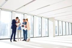 Πλήρες μήκος των επιχειρηματιών που αναθεωρούν τα έγγραφα στο νέο γραφείο στοκ εικόνα με δικαίωμα ελεύθερης χρήσης