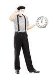 Πλήρες πορτρέτο μήκους ενός αρσενικού mime κρατώντας ένα ρολόι και ένα gesturin Στοκ Εικόνα