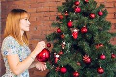 Πλήρες πορτρέτο μήκους της ευτυχούς νέας γυναίκας που διακοσμεί το χριστουγεννιάτικο δέντρο με τη σφαίρα Χριστουγέννων Στοκ Φωτογραφία