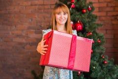 Πλήρες πορτρέτο μήκους της ευτυχούς νέας γυναίκας που διακοσμεί το χριστουγεννιάτικο δέντρο με τη σφαίρα Χριστουγέννων Στοκ Φωτογραφίες
