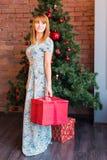 Πλήρες πορτρέτο μήκους της ευτυχούς νέας γυναίκας που διακοσμεί το χριστουγεννιάτικο δέντρο με τη σφαίρα Χριστουγέννων Στοκ φωτογραφίες με δικαίωμα ελεύθερης χρήσης