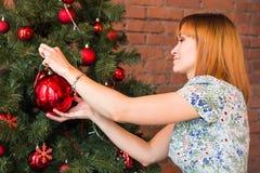 Πλήρες πορτρέτο μήκους της ευτυχούς νέας γυναίκας που διακοσμεί το χριστουγεννιάτικο δέντρο με τη σφαίρα Χριστουγέννων Στοκ εικόνα με δικαίωμα ελεύθερης χρήσης