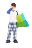 Πλήρες πορτρέτο μήκους του νυσταλέου παιδιού που κρατά ένα μαξιλάρι Στοκ Φωτογραφία