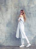 Πλήρες πορτρέτο της γυναίκας μόδας που φορά το άσπρο παλτό, το παντελόνι και τα πάνινα παπούτσια σχεδίου στοκ φωτογραφία με δικαίωμα ελεύθερης χρήσης
