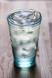 Πλήρες ποτήρι του νερού με τον πάγο στον ξύλινο μετρητή κουζινών Wodd Στοκ Εικόνα
