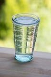 Πλήρες ποτήρι του νερού στον ξύλινο μετρητή κουζινών Πράσινο backgro Στοκ Εικόνες