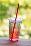 Πλήρες ποτήρι του νερού στον ξύλινο μετρητή κουζινών Φλυτζάνι Plactick Στοκ Φωτογραφίες