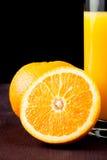 Πλήρες ποτήρι του χυμού από πορτοκάλι κοντά στο μισό πορτοκάλι με το διάστημα για το κείμενο Στοκ φωτογραφία με δικαίωμα ελεύθερης χρήσης