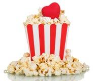 Πλήρες τετραγωνικό κιβώτιο popcorn μια κόκκινη καρδιά που απομονώνεται με στο λευκό Στοκ Εικόνες