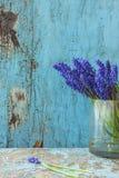 πλήρης άνοιξη λιβαδιών πικραλίδων ανασκόπησης κίτρινη Μπλε λουλούδια σε ένα βάζο γυαλιού φρέσκες τουλίπες ενός στις μπλε παλαιές  Στοκ φωτογραφία με δικαίωμα ελεύθερης χρήσης