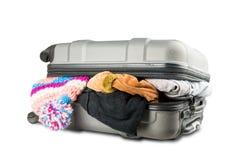 Πλήρης βαλίτσα με τα ενδύματα στο άσπρο υπόβαθρο Στοκ Εικόνες