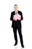 Πλήρης εκμετάλλευση επιχειρηματιών μήκους εύθυμη piggybank Στοκ εικόνες με δικαίωμα ελεύθερης χρήσης