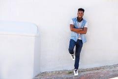 Πλήρης ευτυχής νεαρός άνδρας σωμάτων που κλίνει ενάντια στον τοίχο με τα ακουστικά Στοκ Φωτογραφίες