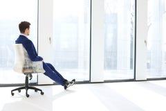 Πλήρης πλάγια όψη μήκους της στοχαστικής νέας συνεδρίασης επιχειρηματιών στην καρέκλα από τα παράθυρα στο νέο γραφείο Στοκ φωτογραφία με δικαίωμα ελεύθερης χρήσης