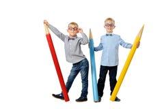 Πλήρη ευτυχή νέα αγόρια πορτρέτου μήκους στα γυαλιά και bowtie τοποθέτηση κοντά στα τεράστια ζωηρόχρωμα μολύβια έννοια εκπαιδευτι Στοκ Εικόνες