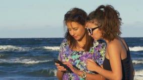 Πλήρους ευφορίας θηλυκοί φίλοι που κουβεντιάζουν και που κοιτάζουν σε ένα smartphone θαλασσίως απόθεμα βίντεο