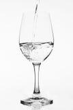 Πλήρωση ενός καθαρού γυαλιού με το νερό στο άσπρο υπόβαθρο Στοκ Φωτογραφίες