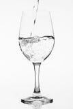 Πλήρωση ενός καθαρού γυαλιού με το νερό στο άσπρο υπόβαθρο Στοκ φωτογραφία με δικαίωμα ελεύθερης χρήσης