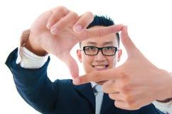 Πλαίσιο δάχτυλων. Χαμογελώντας ασιατικό επιχειρησιακό άτομο που κάνει ένα πλαίσιο με το πτερύγιο στοκ εικόνες