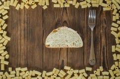Πλαίσιο ζυμαρικών με το ψωμί και δίκρανο στο ξύλινο υπόβαθρο Στοκ Εικόνες