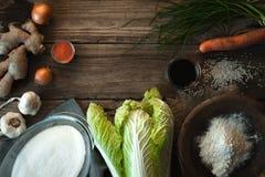Πλαίσιο με το κινεζικό λάχανο και συστατικά για το kimchi σε έναν ξύλινο πίνακα Στοκ Φωτογραφίες
