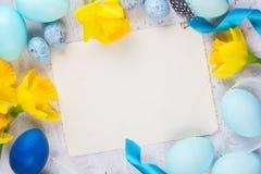 Πλαίσιο Πάσχας με τα χρωματισμένα αυγά και τα λουλούδια Στοκ Φωτογραφία
