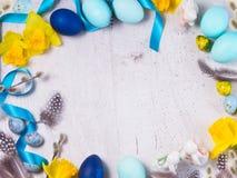 Πλαίσιο Πάσχας με τα χρωματισμένα αυγά και τα λουλούδια Στοκ Εικόνες