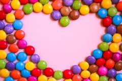 Πλαίσιο της μορφής καρδιών πολύχρωμων καραμελών στο ρόδινο υπόβαθρο Στοκ Εικόνα