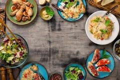 Πλαίσιο του risotto, των ψημένων ποδιών κοτόπουλου και των πρόχειρων φαγητών Στοκ Εικόνες