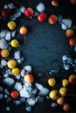 Πλαίσιο των μήλων στο χιόνι στη σκοτεινή κατακόρυφο υποβάθρου Στοκ Φωτογραφία