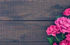 Πλαίσιο των τριαντάφυλλων στο σκοτεινό αγροτικό ξύλινο υπόβαθρο just rained Στοκ Φωτογραφία