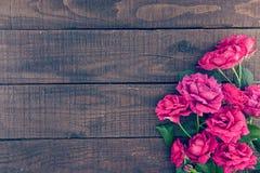 Πλαίσιο των τριαντάφυλλων στο σκοτεινό αγροτικό ξύλινο υπόβαθρο just rained Στοκ εικόνα με δικαίωμα ελεύθερης χρήσης