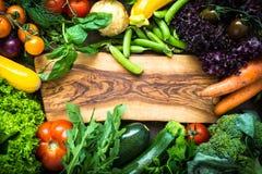 Πλαίσιο των φρέσκων λαχανικών γύρω από τον τέμνοντα πίνακα Στοκ Φωτογραφίες