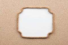 Πλαίσιο φιαγμένο από σχοινί με ένα άσπρο υπόβαθρο στην άμμο Στοκ Φωτογραφίες