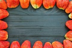 Πλαίσιο φραουλών μαύρο σε ξύλινο Στοκ εικόνα με δικαίωμα ελεύθερης χρήσης