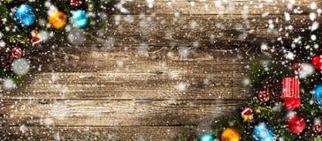 Πλαίσιο Χαρούμενα Χριστούγεννας με το χιόνι και το πραγματικά ξύλινα πράσινα πεύκο και τα μπιχλιμπίδια Στοκ εικόνα με δικαίωμα ελεύθερης χρήσης
