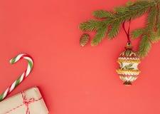Πλαίσιο Χριστουγέννων στο κόκκινο υπόβαθρο Πράσινοι κλάδοι έλατου, δώρα Χριστουγέννων, διακοσμήσεις και κάλαμοι καραμελών Η τοπ ά Στοκ εικόνα με δικαίωμα ελεύθερης χρήσης