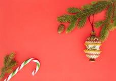 Πλαίσιο Χριστουγέννων στο κόκκινο υπόβαθρο Πράσινοι κλάδοι έλατου, διακόσμηση Χριστουγέννων και κάλαμος καραμελών Η τοπ άποψη, επ Στοκ Εικόνες