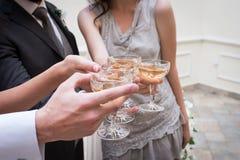 πλαισιωμένα σαμπάνια γυαλιά που καλύπτονται οριζόντια Γαμήλιοι φιλοξενούμενοι που τα γυαλιά σαμπάνιας με τα newlywed's στοκ εικόνα