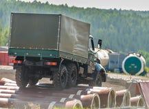 Πλαισιωμένες κουρτίνα κινήσεις φορτηγών στο εμπόδιο από τους σωλήνες Στοκ Εικόνες