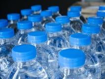 Πλαστικά καλύμματα μπουκαλιών νερό στις σειρές που πίνουν το προϊόν Στοκ Εικόνες