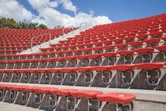 Πλαστικά κόκκινα καθίσματα στο γήπεδο ποδοσφαίρου ή το αμφιθέατρο Στοκ Εικόνες