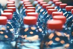Πλαστικά μπουκάλια με τα κόκκινα καλύμματα Στοκ Φωτογραφίες