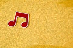 Πλαστική αυτοκόλλητη ετικέττα σημειώσεων μουσικής στο ζωηρόχρωμο τοίχο τσιμέντου Στοκ Εικόνες