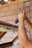 Πλαστική εγκατάσταση παραθύρων Ο εργαζόμενος συνδέει το πιάτο αγκύρων με το κατσαβίδι στοκ εικόνες με δικαίωμα ελεύθερης χρήσης